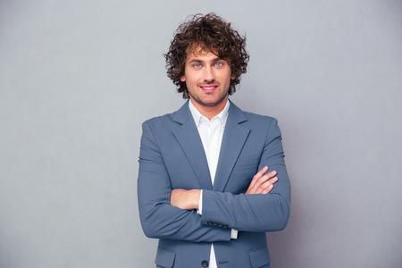 Ritratto di un uomo d'affari allegro in piedi con le braccia piegate su sfondo grigio