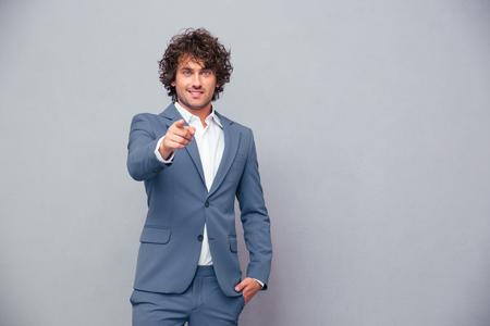 Retrato de un hombre de negocios feliz apuntando el dedo a la cámara sobre fondo gris