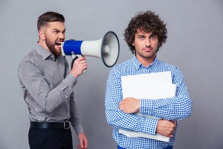 camisa: Hombre de negocios enojado gritando a trav�s de meg�fono a otro hombre sobre fondo gris