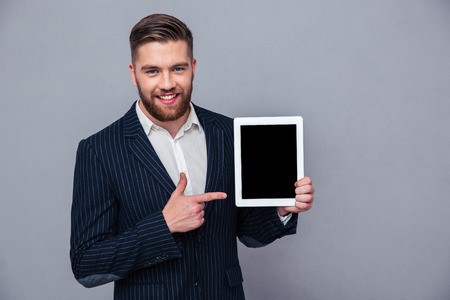 Portrait of a smiling businessman pointing finger on tablet computer screen over gray background