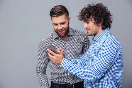 Portrait d'un deux hommes heureux utilisez un Smartphone sur fond gris Banque d'images - 45839521