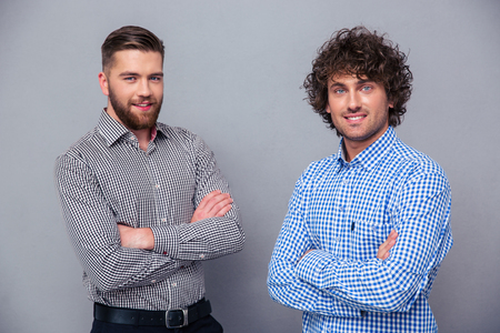 Portrait of a two happy men standing with arms folded on gray background Stock Photo