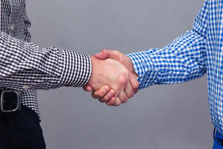 stretta di mano: Ritratto di un due mani maschili che fanno stretta di mano su sfondo grigio