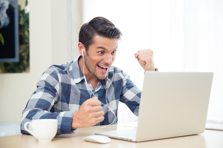 win: Portrait of a casual man watching the game on his laptop at home Stock Photo