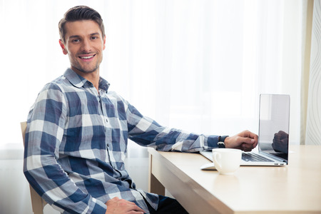 only one man: Portrait of a happy man sitting at the table with laptop and looking at camera