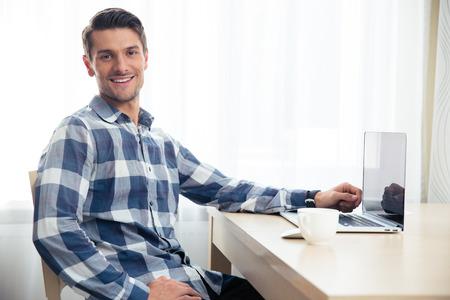 caras: Retrato de un hombre feliz sentado en la mesa con ordenador port�til y mirando a la c�mara Foto de archivo