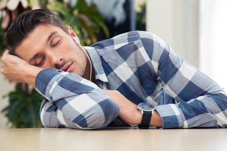 sleeping tablets: Portrait of a casual man sleeping at the table at home