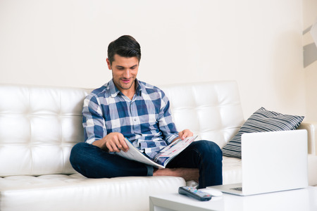 Portrait of a man reading magazine on the sofa at home Stock Photo