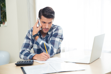 Handsome man making notes on the bills while talking on the phone at home Stock Photo