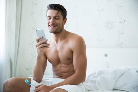 männer nackt: Portrait eines glücklichen Mann mit Zahnbürste und mit Smartphone im Schlafzimmer