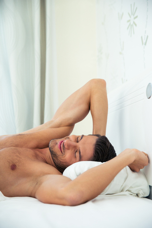 desnudo: Retrato de un hombre hermoso que descansa sobre la cama en su casa