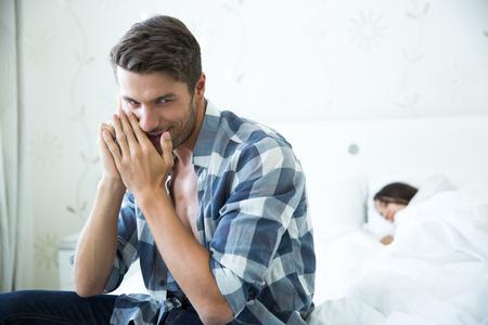 cama: Retrato de un hombre hablando por tel�fono mientras su mujer durmiendo en la cama en su casa