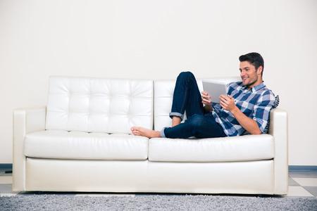 using the computer: Retrato de un hombre casual acostado en el sofá con el ordenador tableta