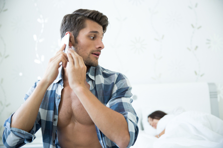 husband: Portrait of a handsome man talking on the phone while his wife sleeping in the bed at home Stock Photo
