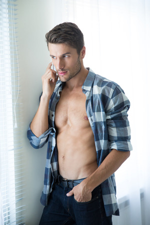 male model torso: Portrait of a young man with perfect body talking on the phone and looking in window at home