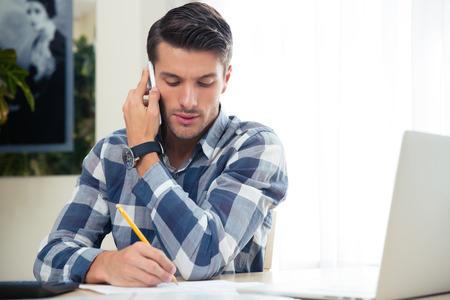 Portret van een man het maken van notities op de rekeningen tijdens het praten aan de telefoon thuis