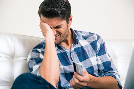 creditor: Portrait of a sad man holding bank card at home Stock Photo