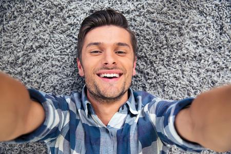 beau jeune homme: Portrait d'un homme souriant allong� sur le sol et faire selfie photo Banque d'images