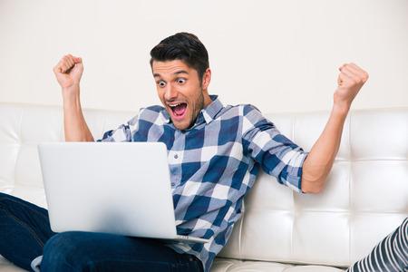 usando computadora: Retrato de hombre emocionado mirando juego en la computadora portátil en casa Foto de archivo