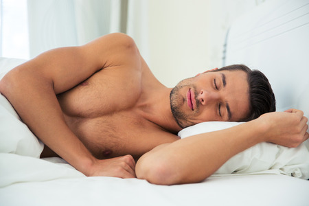 naked male body: Portrait of a handsome man sleeping on the bed at home