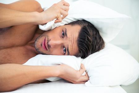 persona enferma: Retrato de un hombre guapo acostado en la cama con la almohada en la cabeza en su casa