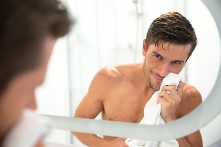 Portret van een man met een handdoek kijken naar zijn spiegelbeeld in de spiegel in de badkamer