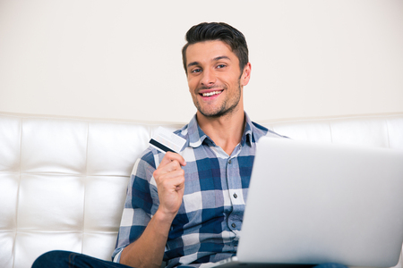 man holding card: Portrait of a happy man sitting on the coach with bank card and laptop at home