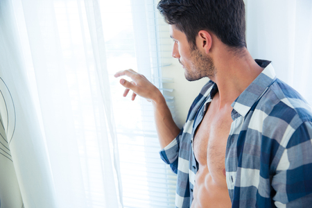 handsome guy: Portrait of a handsome man looking in window at home Stock Photo