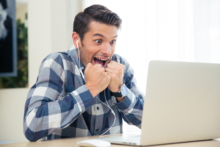 Portrait of a cheerful man watching the game on his laptop at home