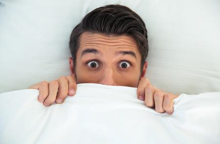 asustado: Hombre que oculta en la cama bajo la manta en el país Foto de archivo