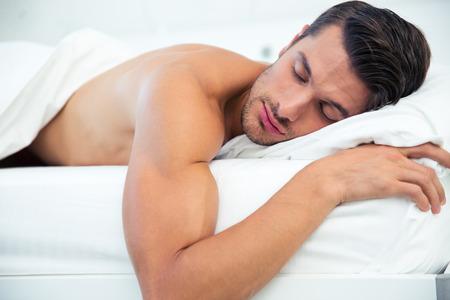 nude young: Портрет человека, спящего в постели у себя дома Фото со стока