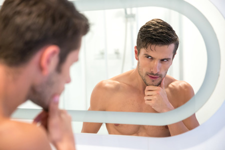 metrosexual: Portrait of a handsome man looking at his reflection in the mirror in bathroom