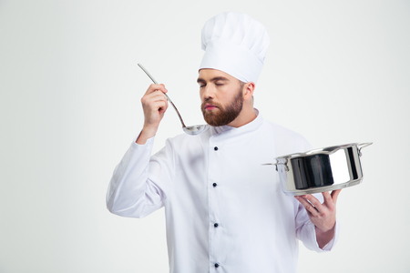 toque blanche: Portrait of a male chef cook holding a saucepan and ladle isolated on a white background