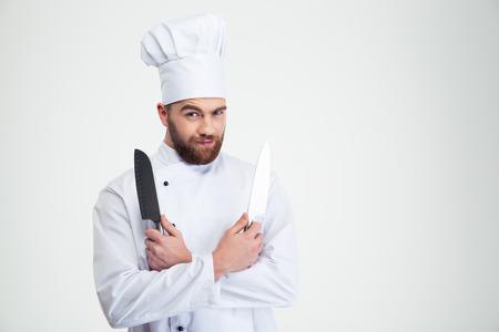cocinero: Retrato de un cocinero de sexo masculino guapo cocinar sosteniendo cuchillos aislados en un fondo blanco Foto de archivo