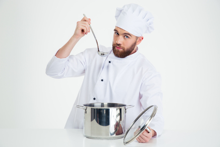 toque blanche: Portrait of a handsome male chef cook tasting food isolated on a white background Stock Photo