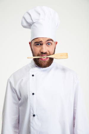 Portrait of a handsome male chef cook holding spoon in teeth isolated on a white background Stock Photo