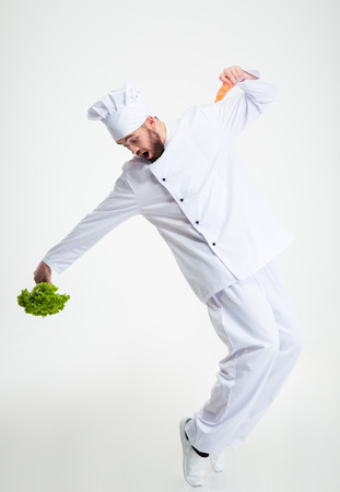 Full length portrait of a funny chef cook holding vegetables and dancing isolated on a white background Imagens