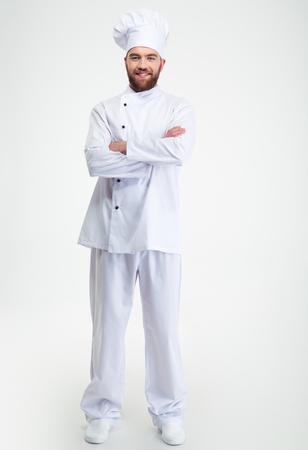 笑顔の男性シェフの完全な長さの肖像画調理白い背景に分離した腕を組んで立っています。