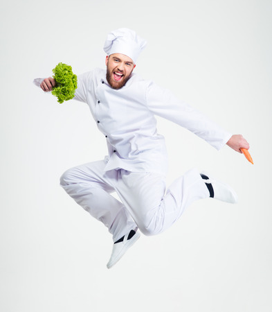 Full length portrait of a cheerful chef cook dancing isolated on a white background