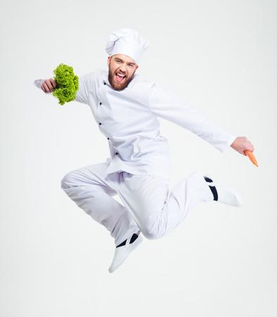uniformes: Retrato de cuerpo entero de un cocinero alegre cocinero bailando aislado en un fondo blanco