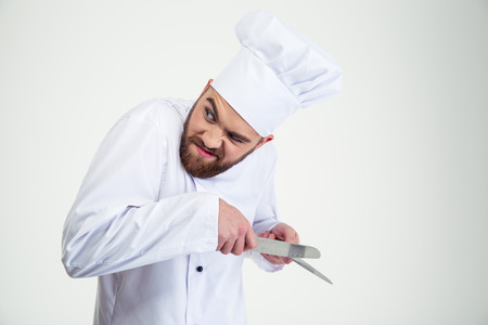 severance: Portrait of a male chef cook sharpening knife isolated on a white background