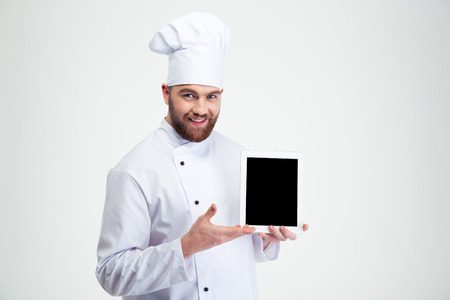 白い背景に分離された空白のタブレット コンピューターの画面を示す幸せな男性シェフ クックの肖像画 写真素材
