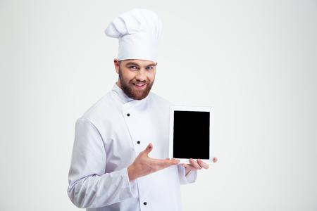 cocinero: Retrato de un cocinero de sexo masculino feliz cocinero que muestra la pantalla de tablet PC en blanco aislado en un fondo blanco