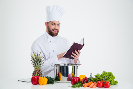 Portrait of a happy male chef cook holding recipe book and preparing portrait of a happy male chef cook holding recipe book and preparing food isolated on a forumfinder Gallery