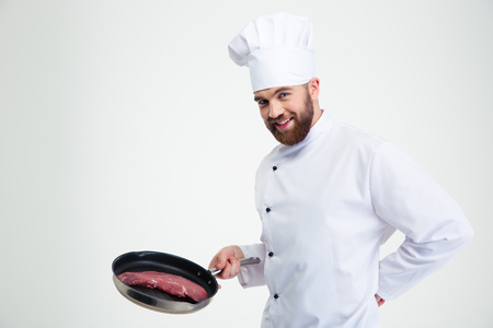 pan: Portrait of a cheerful chef cook holding fresh meat on pan isolated on a white background