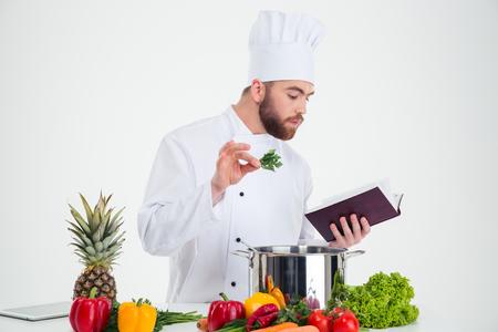 cocinero: Retrato de un cocinero de sexo masculino hermoso cocinar lectura libro de recetas mientras se prepara el alimento aislado en un fondo blanco