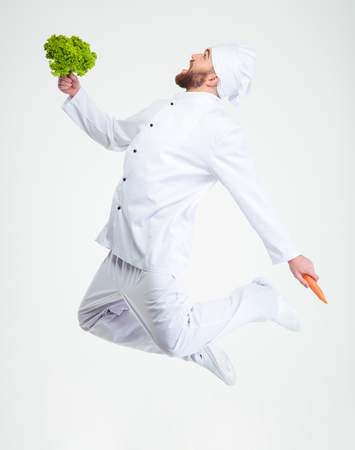 Full length portrait of a funny chef cook dancing with vegetables isolated on a white background