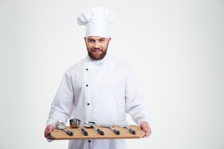 chef: Retrato de un cocinero de sexo masculino sonriente cocinar sosteniendo tabla de cortar de madera con cucharas aisladas sobre un fondo blanco