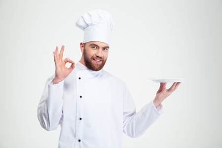 chef uniform: Portrait of a man chef showing ok sign and empty plate isolated on a white background