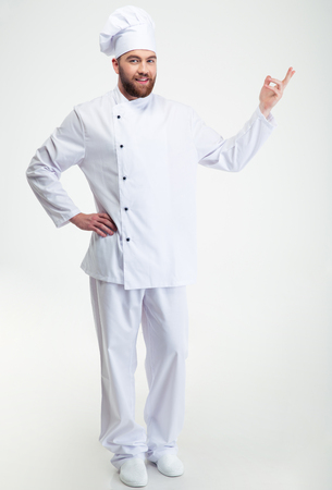 welcome: Full length portrait of a happy chef cook showing welcome gesture isolated on a white background Stock Photo